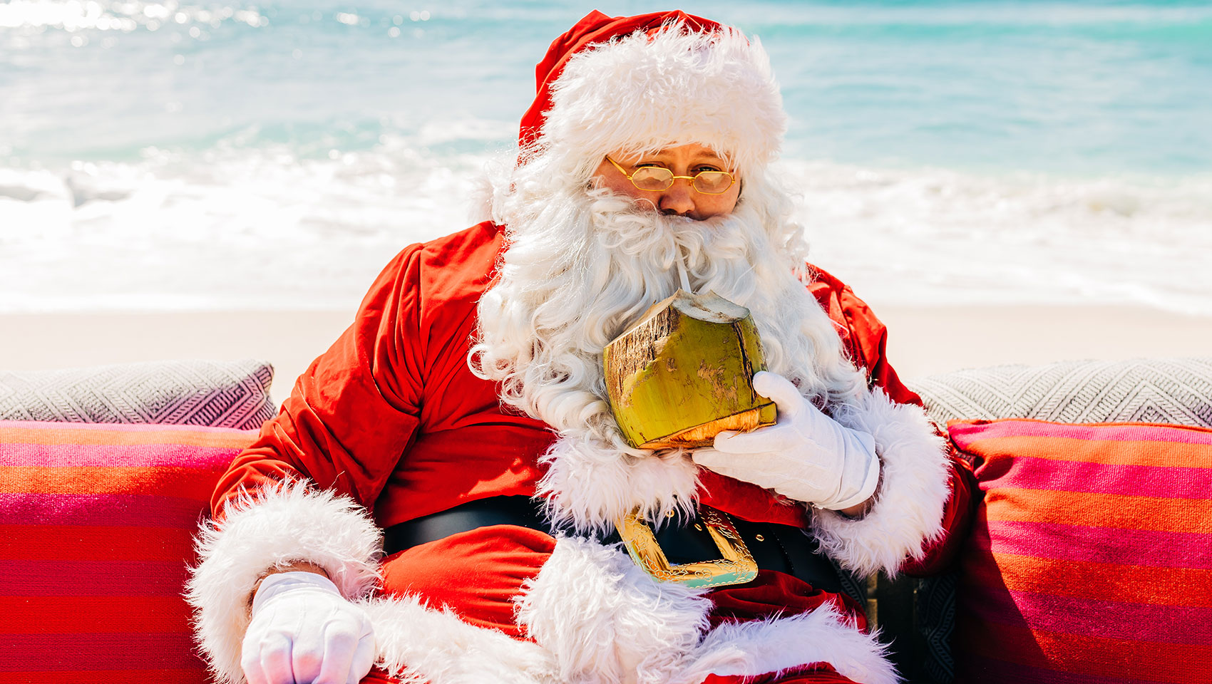 Festive at Kimpton Seafire - Santa sitting on chair on beach with a coconut drink