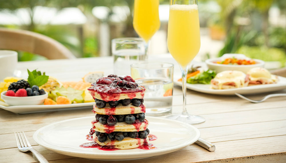 two mimosas at our outdoor seating table with a stack of pancakes in front and two other dishes in the background.